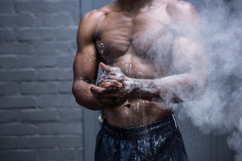 Young Bodybuilder shaking Chalk off his hands stock photography