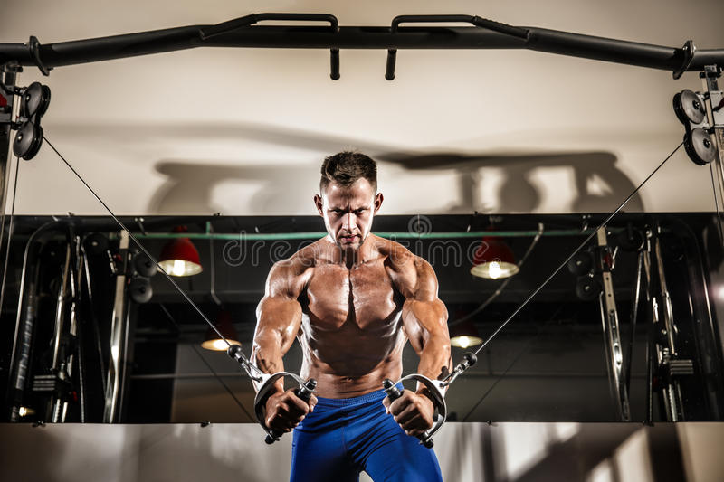 Young Bodybuilder Is Working With Cable Crossover In Gym. Young Bodybuilder Is Working On His Chest With Cable Crossover In Gym royalty free stock image