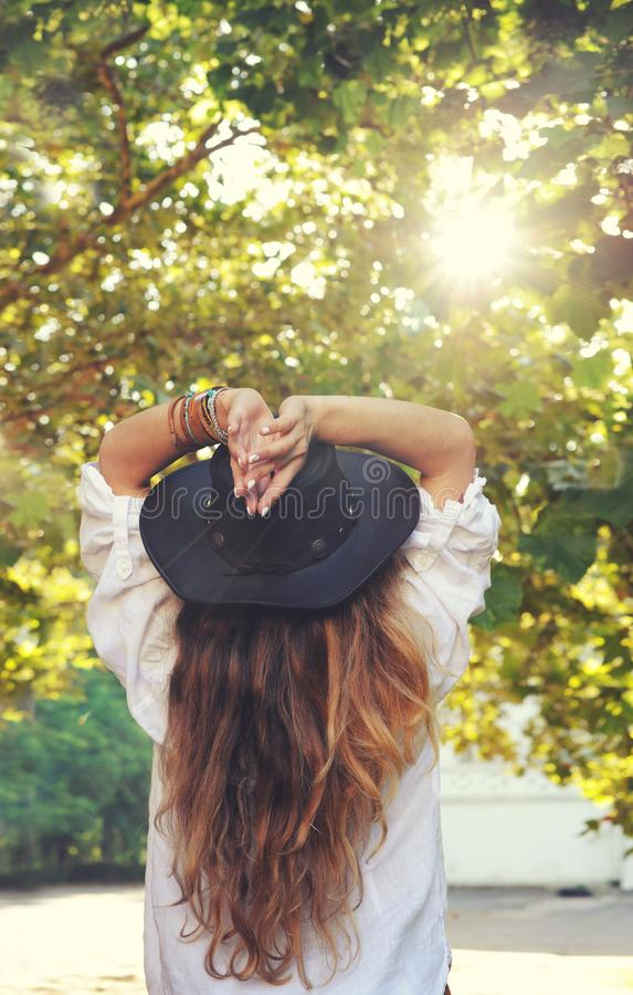 Young boho style woman enjoy sunlight in summer park, hippie, indie style, chic leather black hat, long hair, travel concept, back stock images