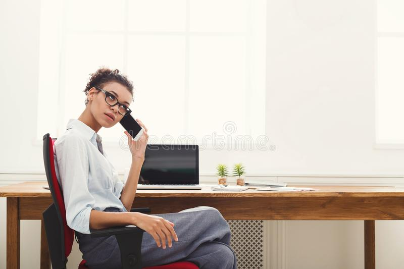 Business talk, bored woman talking on phone at office royalty free stock image