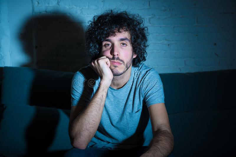 Portrait of bored sleepless young man sitting on the couch watching TV at night stock images