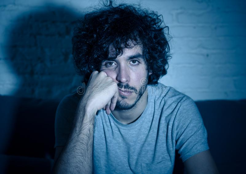 Portrait of bored sleepless young man sitting on the couch watching TV at night royalty free stock photos