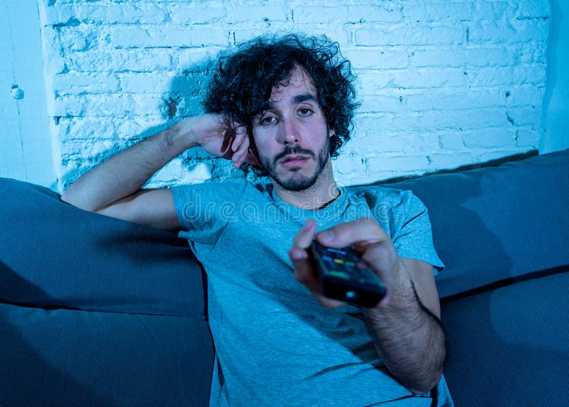 Portrait of bored sleepless young man sitting on the couch watching TV at night stock photo