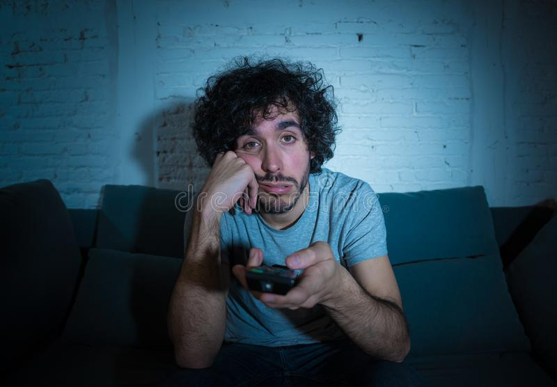 Portrait of bored sleepless young man sitting on the couch watching TV at night stock photos