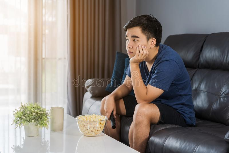 Bored man watching tv and sitting on sofa in the living room royalty free stock images