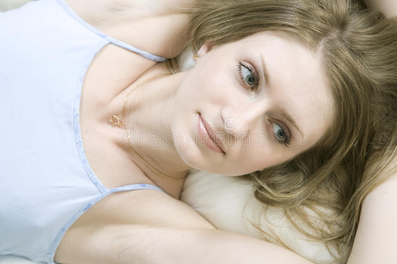 Young Bored Woman Lying Down On The Bed Stock Photo