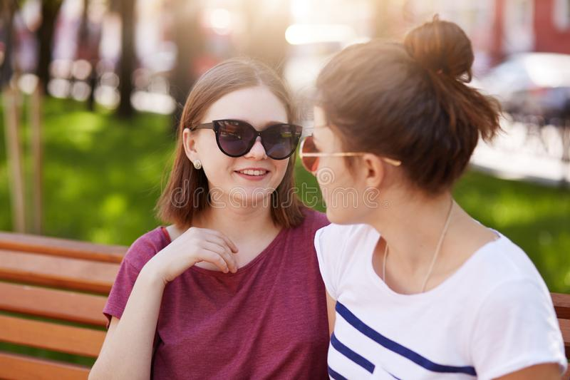 Young bosom friends have long and interesting discussion together after not seeing each other for long time. Affectionate smiling stock photography
