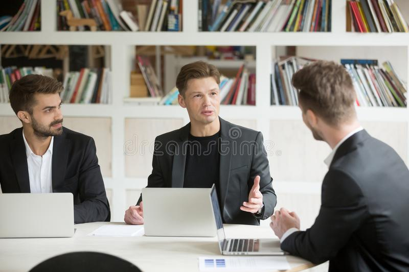 Young boss instructing employees during briefing meeting. stock images