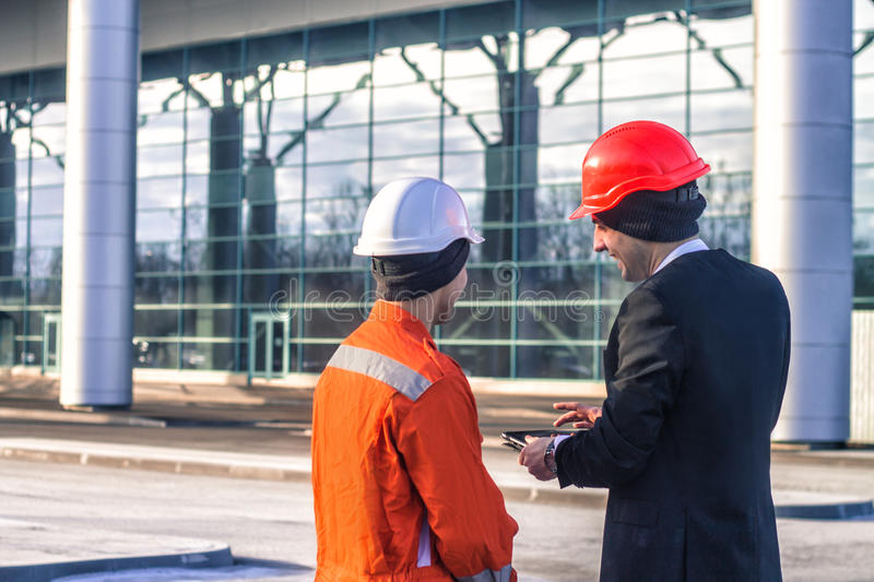 Young boss and worker i discussing construction project on table royalty free stock photo
