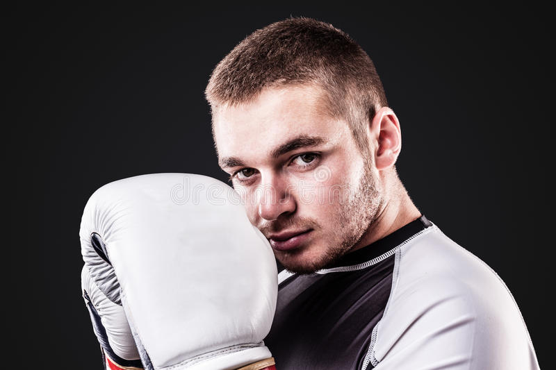 Young boxer on black. A young kickboxer or boxer isolated over a black background stock photo