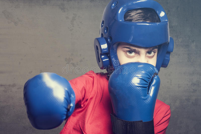 Young boxer. Young boy fighting wearing blue gloves and helmet. Martial arts kids concept royalty free stock photos
