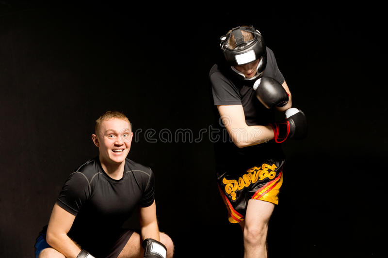 Young boxer ducking under his opponents punch. With a smile of glee as the men is pulled off balance by the power of his own punch stock photo