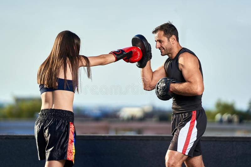 Young woman boxer hitting pads outdoor. Young boxer girl with her coach hitting mitts outdoor on a roof in urban environment royalty free stock photography