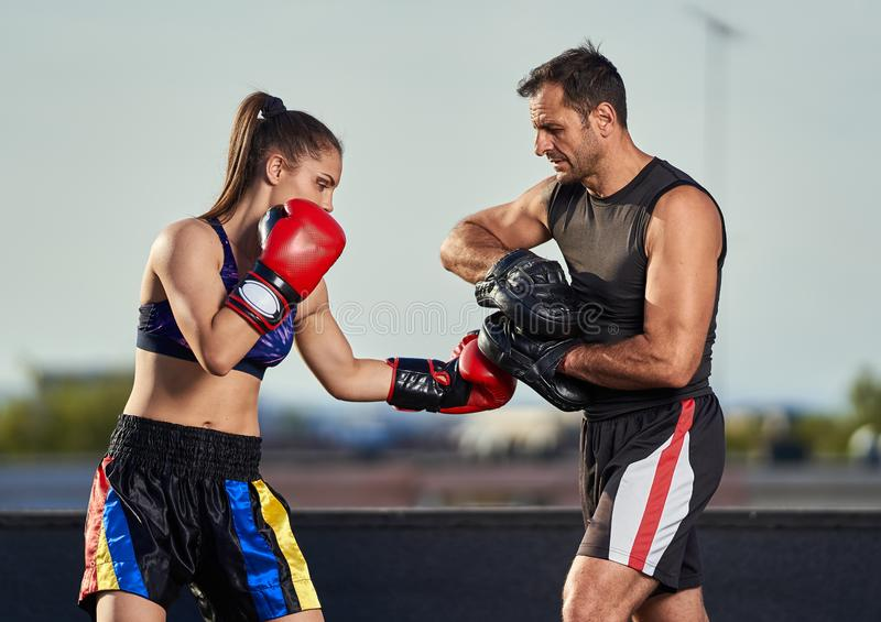 Young woman boxer hitting pads outdoor. Young boxer girl with her coach hitting mitts outdoor on a roof in urban environment royalty free stock photos