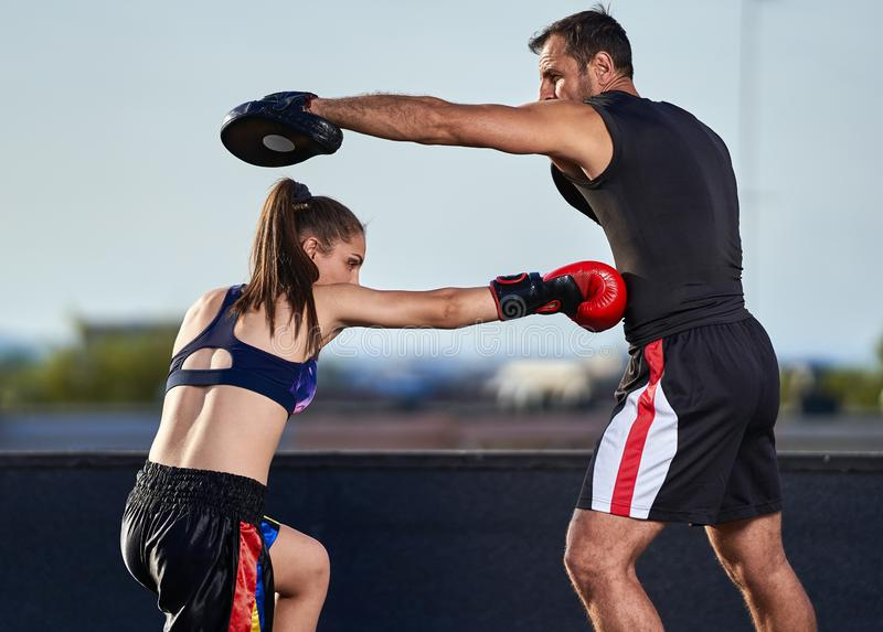 Young woman boxer hitting pads outdoor. Young boxer girl with her coach hitting mitts outdoor on a roof in urban environment royalty free stock image