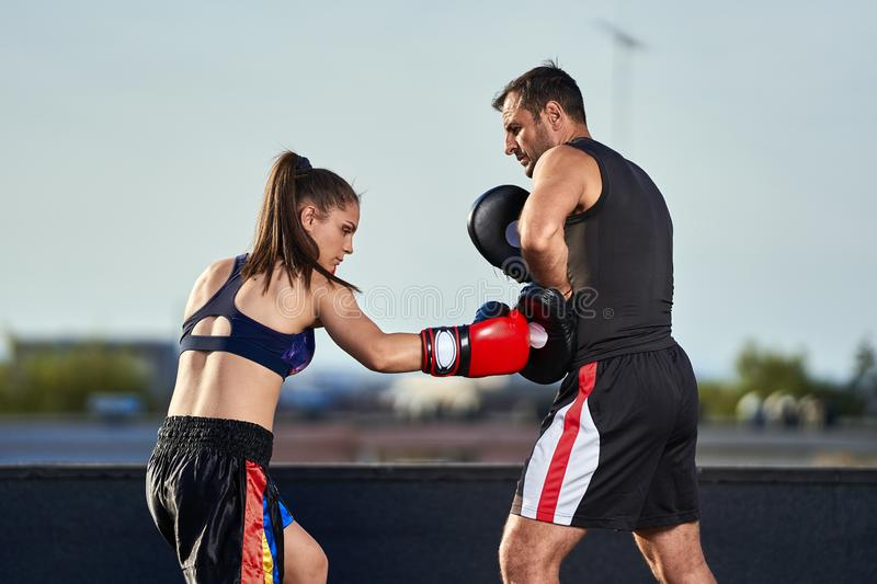Young woman boxer hitting pads outdoor. Young boxer girl with her coach hitting mitts outdoor on a roof in urban environment stock images