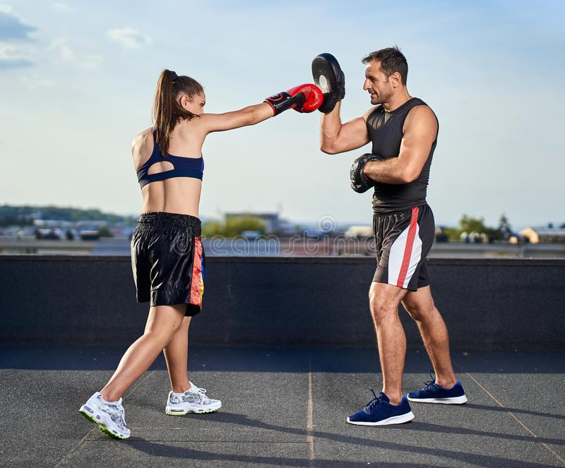 Young woman boxer hitting pads outdoor. Young boxer girl with her coach hitting mitts outdoor on a roof in urban environment stock image