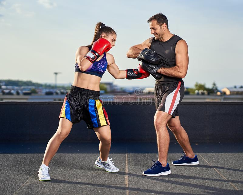 Young woman boxer hitting pads outdoor royalty free stock photo
