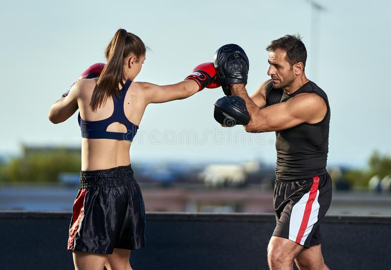 Young woman boxer hitting pads outdoor. Young boxer girl with her coach hitting mitts outdoor on a roof in urban environment stock photography