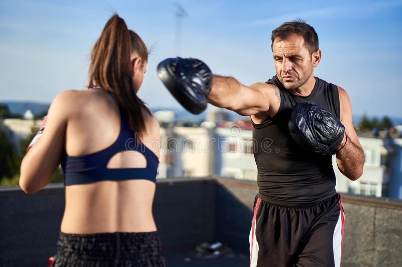 Young woman boxer hitting pads outdoor. Young boxer girl with her coach hitting mitts outdoor on a roof in urban environment stock photos