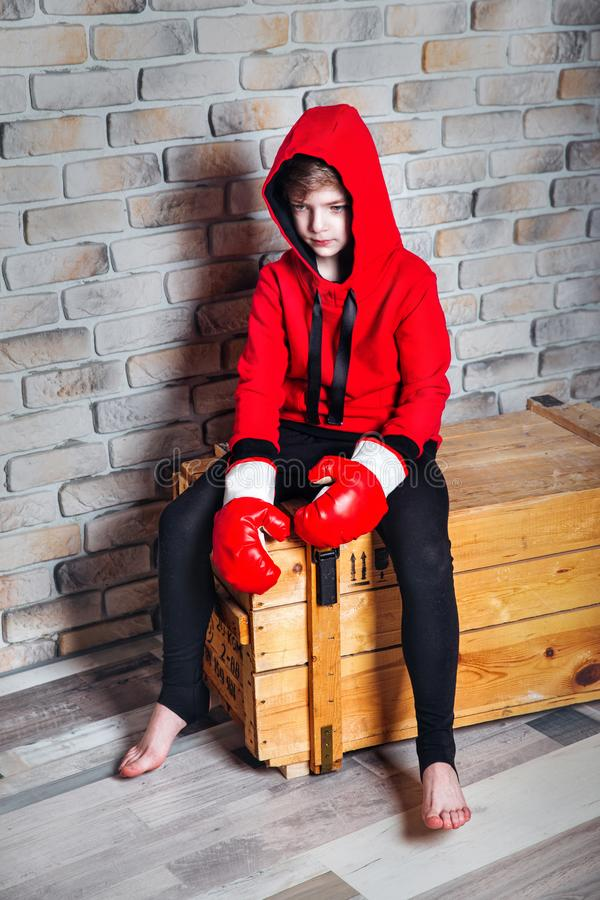 Little boy boxer with blonde hair dressing in red sweatshirt wearing boxing gloves posing in a studio. royalty free stock images