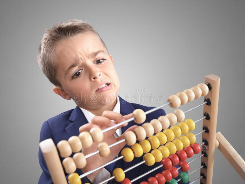 Young boy accountant businessman does calculation on a abacus royalty free stock images