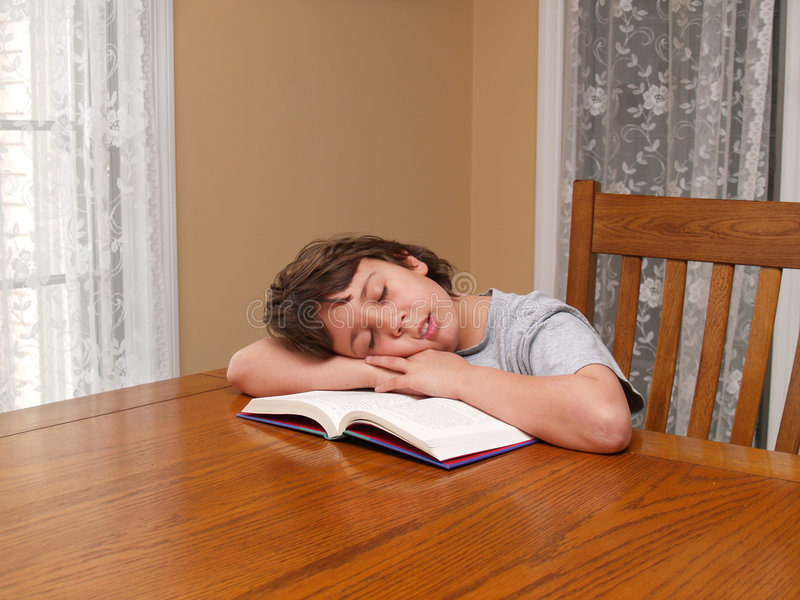 Young boy asleep while reading. A young boy sitting at a table that fell asleep while reading a book royalty free stock photography