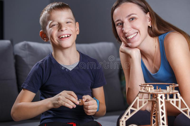 Young boy assembling constructor with his mother. royalty free stock image