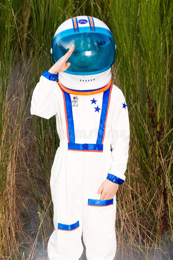 Young boy in an astronaut suit saluting stock images