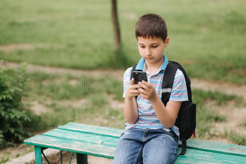 Young boy with backpack sitting on the bench and play online games during school break royalty free stock photography