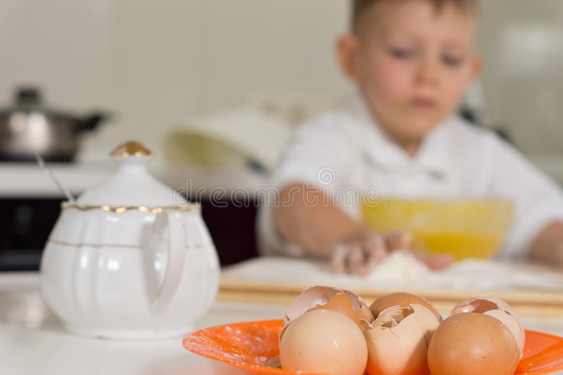 Young boy baking in the kitchen using eggs. With close up focus to all the broken egg shells on a plate in front of him stock photo