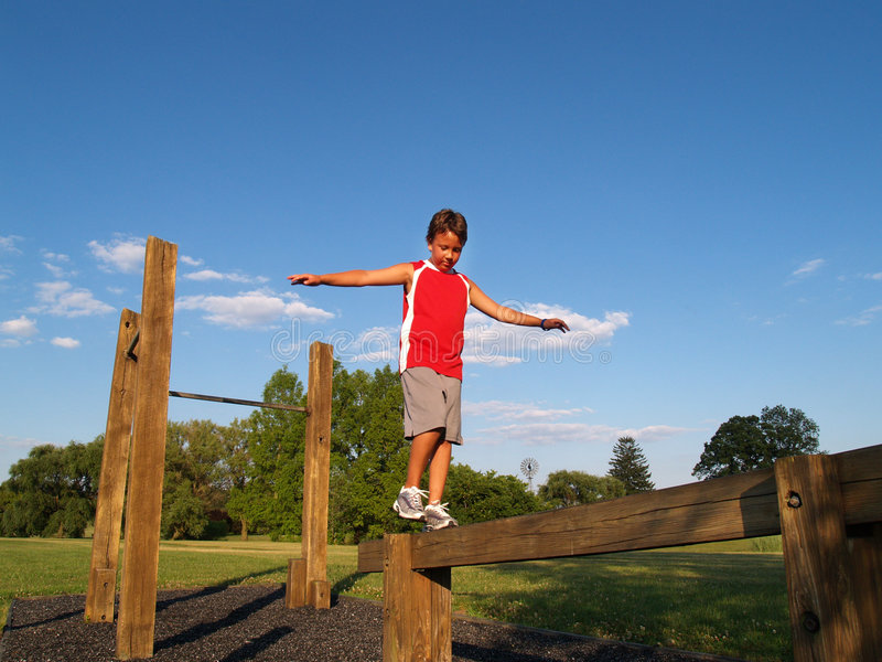 Young boy on a balance beam stock images