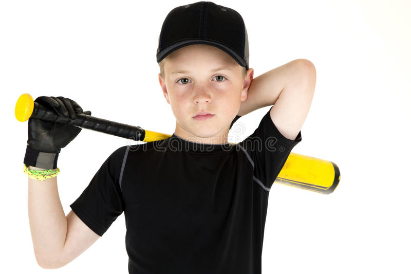 Young boy baseball player holding his bat with a serious express. Boy baseball player holding bat with a serious expression stock photos