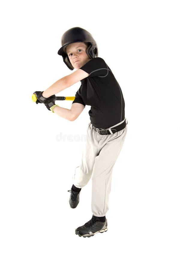 Young boy baseball player swinging bat with eyes open. Boy baseball player batting with eyes open stock photo