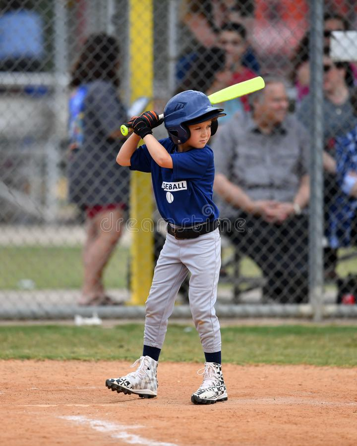 Young Boy batting during a Little League baseball game. Little league baseball player during a YMCA baseball game. Boy is at the plate swinging the bat and royalty free stock image