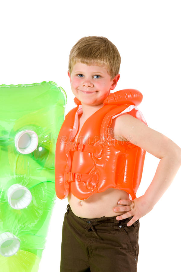 Young boy with beach mattress. Little boy wearing orange life vest, holding green inflatable mattress. Isolated on white stock image