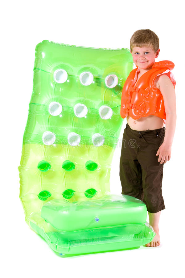 Young boy with beach mattress. Little boy wearing orange life vest, holding green inflatable mattress. Isolated on white royalty free stock photo