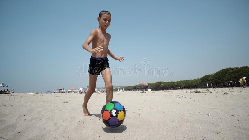 Young boy at the beach plays football ball royalty free stock photos