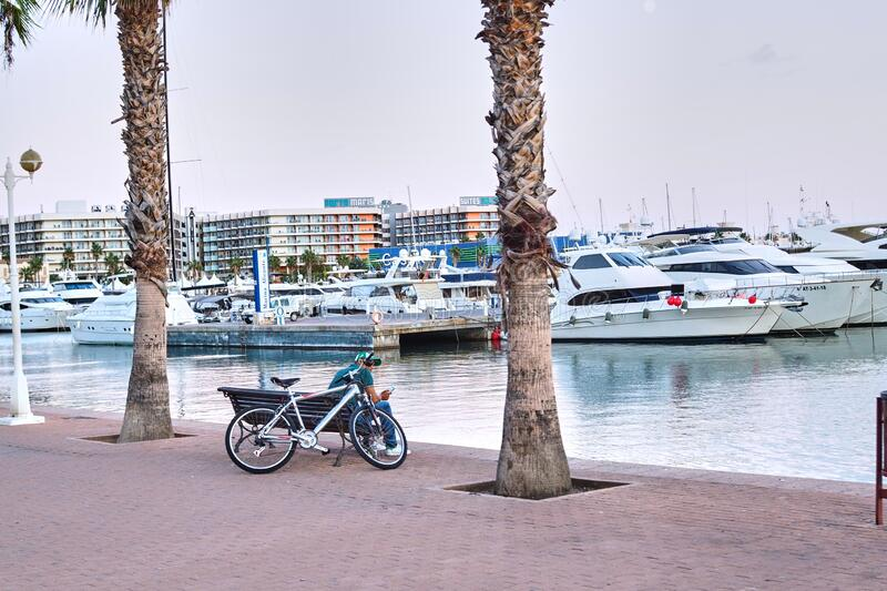 Young boy with bicycle looking at the sea. In Alicante stock photo