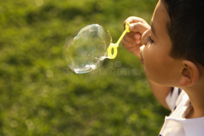 Young Boy Blowing Bubbles royalty free stock photography