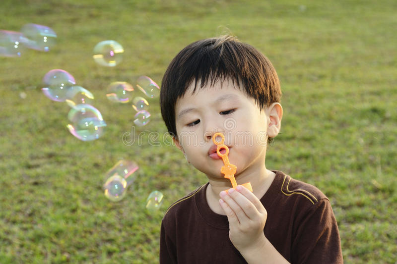 Download Young boy blowing bubbles stock image. Image of grass - 13461843