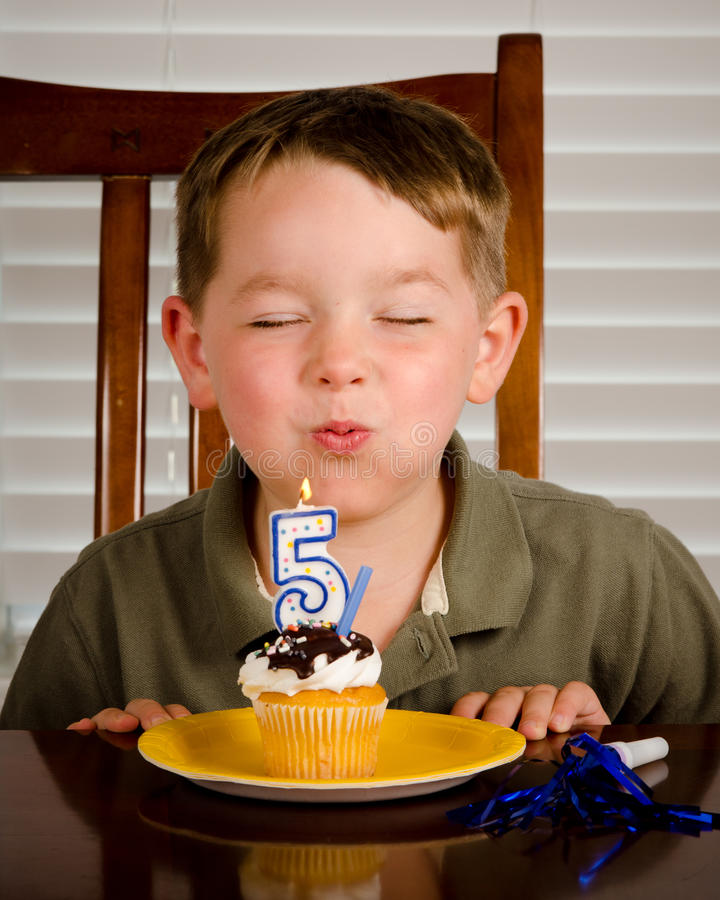 Young boy blowing out birthday candle royalty free stock photo