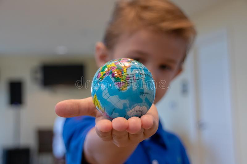 Young boy in blue shirt holding a small Earth Globe in his hands. The Future of The Earth is in our Children`s Hands. royalty free stock image