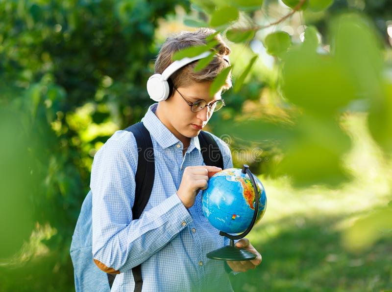 Young boy in blue shirt and round glasses looks and points on globe in his hands. Education, back to school royalty free stock photo