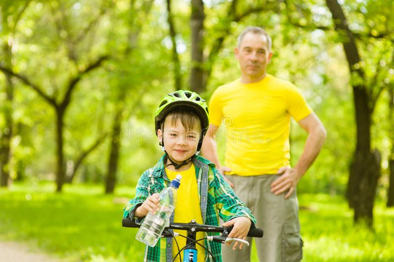 Young boy with a bottle of water is learning to ride a bike with his grandfather royalty free stock photo