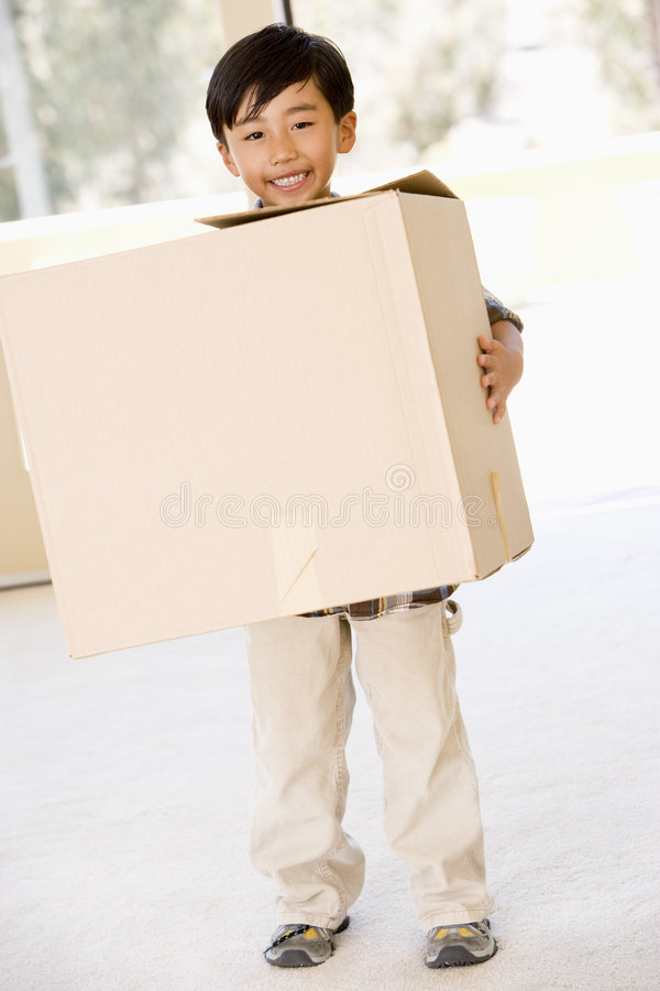 Young boy with box in new home smiling stock photo