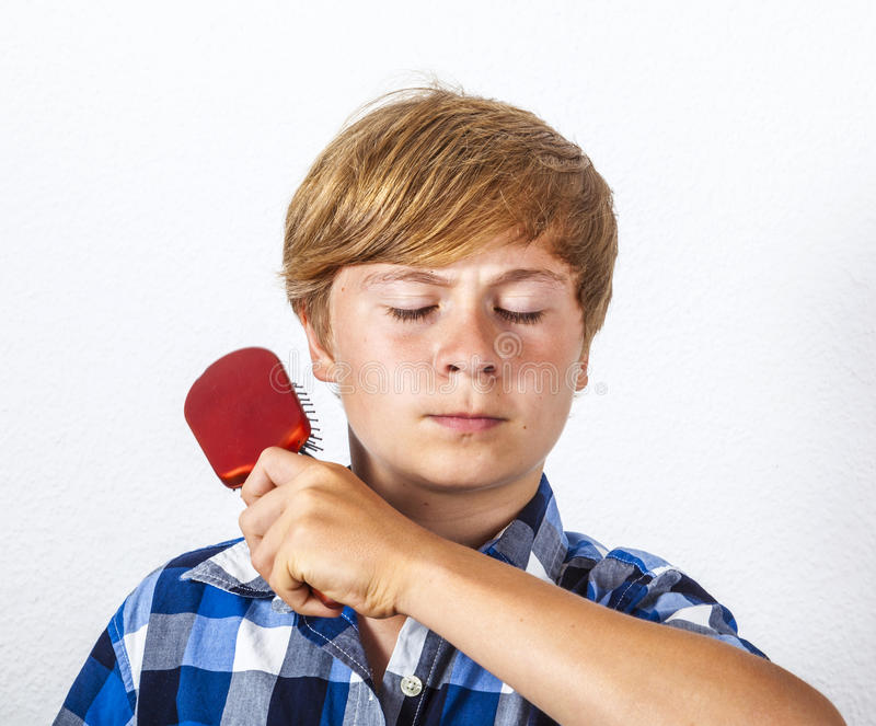 Young boy brushing his hair. With a red brush royalty free stock photography