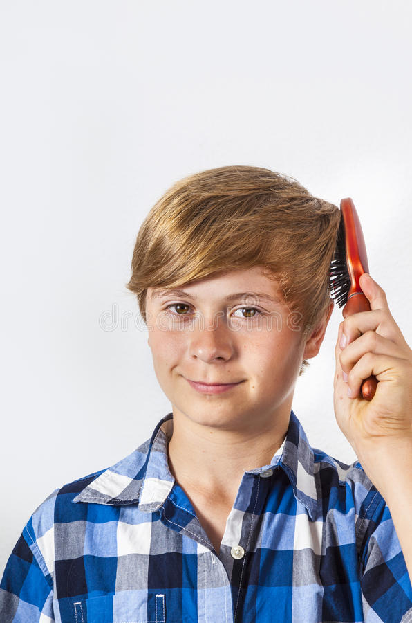 Young boy brushing his hair. With a red brush royalty free stock images