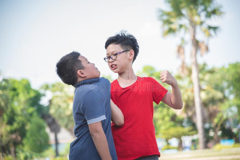 Young boy bullying a boy in park. Young asian boy bullying a boy in park at school royalty free stock images