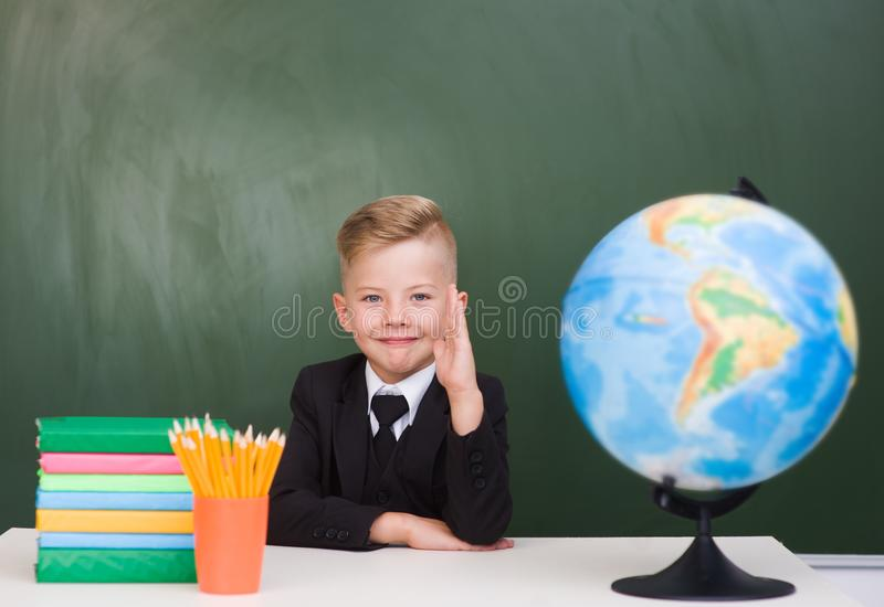 Young boy in a business suit raising hand knowing the answer to the question.  royalty free stock photo